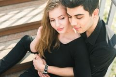 Beautiful young multiracial couple, student couple in love, sit wooden staircase in the city. Beautiful Turkish brunette guy hug a. Caucasian girl in black stock photography