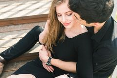 Beautiful young multiracial couple, student couple in love, sit wooden staircase in the city. Beautiful Turkish brunette guy hug a. Caucasian girl in black stock image