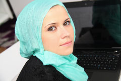 Beautiful young muslim business woman with laptop in office Stock Photo