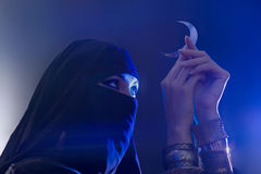 Beautiful young muslim girl holding a moon symbol, spirituality. Beautiful young muslim girl with hijab and jewelry holding a moon symbol, spirituality Royalty Free Stock Image