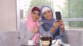 Beautiful Young Muslim Girls do selfie on a smartphone.  Stock Photos