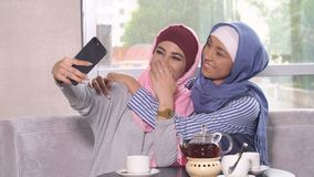 Beautiful Young Muslim Girls do selfie on a smartphone.  Stock Images