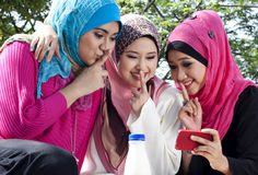 Beautiful young muslim girls having fun. Taking picture with hand phone at park Stock Image