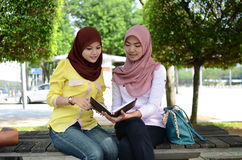 Beautiful young muslim student sharing info together Stock Images