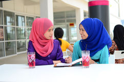 Beautiful young muslim student sharing info together Royalty Free Stock Images