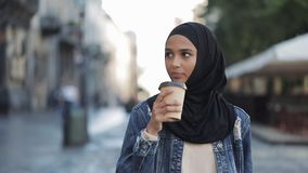 Beautiful young Muslim woman an attractive appearance drinking coffee and walking down the city street. stock video footage