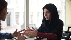 Beautiful young muslim woman in black hijab is talking to her female caucasian friend while sitting in Coffee Shop. Women in good mood, smiling with laptop and stock video
