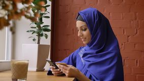 Beautiful young muslim woman in blue hijab rewriting info from card to her phone, sitting in modern cafe.  stock video footage