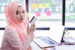 Beautiful young muslim woman showing a credit card with laptop mockup in office stock photo