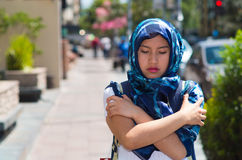 Beautiful young muslim woman wearing blue colored hijab and backpack,, interacting being cold rubbing arms using hands. In street, serious facial expression Stock Photos