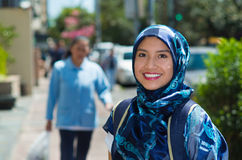 Beautiful young muslim woman wearing blue colored hijab and backpack, posing happily in street smiling to camera Royalty Free Stock Image