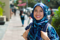 Beautiful young muslim woman wearing blue colored hijab and backpack, posing happily in street smiling to camera. Outdoors urban background Royalty Free Stock Photography