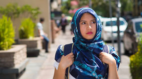 Beautiful young muslim woman wearing blue colored hijab and backpack, posing with thoughtful serious facial expression Royalty Free Stock Photos