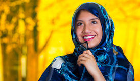 Beautiful young muslim woman wearing blue colored hijab, facing camera posing happily, autumn forest background.  Royalty Free Stock Photography