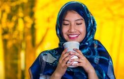 Beautiful young muslim woman wearing blue colored hijab, facing camera posing happily, holding white coffee mug, autumn Stock Photo