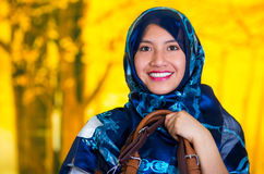 Beautiful young muslim woman wearing blue colored hijab, holding leather purse, facing camera posing happily, autumn Royalty Free Stock Photography