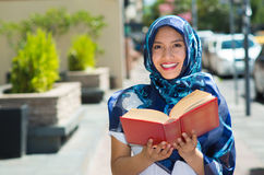 Beautiful young muslim woman wearing blue colored hijab, holding thick reed book and reading in street, outdoors urban. Background Royalty Free Stock Photos