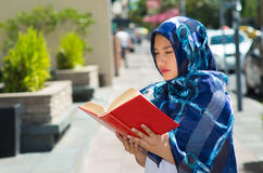 Beautiful young muslim woman wearing blue colored hijab, holding thick reed book and reading in street, outdoors urban. Background Stock Image