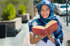 Beautiful young muslim woman wearing blue colored hijab, holding thick reed book and reading in street, outdoors urban. Background Stock Photography