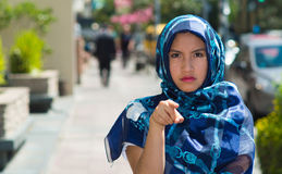 Beautiful young muslim woman wearing blue colored hijab, pointing finger with serious facial expression, outdoors urban. Background Stock Image