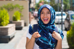 Beautiful young muslim woman wearing blue colored hijab, pointing finger smiling, outdoors urban background.  Stock Photography