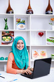 Beautiful young muslim woman working on her laptop
