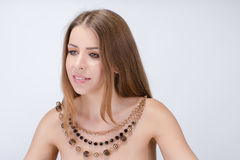 Beautiful young naked woman wearing necklace. Smiling on white background. fashion shoot Stock Photography