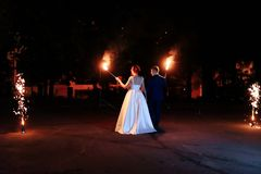 Beautiful young newlywed couple with fire torches in their hands and fireworks 1. Beautiful young newlywed couple with fire torches in their hands and fireworks royalty free stock images