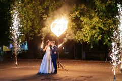 Beautiful young newlywed couple with fire torches in their hands and fireworks 1. Beautiful young newlywed couple with fire torches in their hands and fireworks royalty free stock image