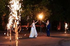 Beautiful young newlywed couple with fire torches in their hands and fireworks 1. Beautiful young newlywed couple with fire torches in their hands and fireworks stock image
