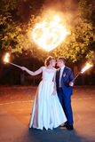 Beautiful young newlywed couple with fire torches in their hands and fireworks 1. Beautiful young newlywed couple with fire torches in their hands and fireworks royalty free stock photography