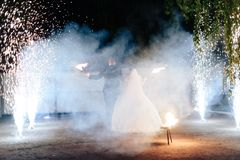 Beautiful young newlywed couple with fire torches in their hands and fireworks 1. Beautiful young newlywed couple with fire torches in their hands and fireworks stock images