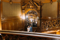 Beautiful young newlywed couple posing on amazing antique stairs with the background of royal wooden vintage interior Royalty Free Stock Photos