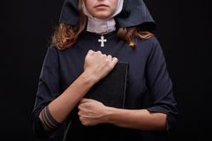 Pretty religious nun in religion concept against dark background. Beautiful young nun in religion black suit holds Bible and posing on camera with big book on a Stock Photography