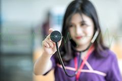 Beautiful young nurse holding stethoscope and  listening to gree. N pulse and heart rates Royalty Free Stock Photo