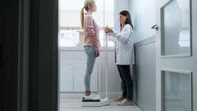 Beautiful young nutritionist woman weighing and measuring his patient on the scale in consultation.