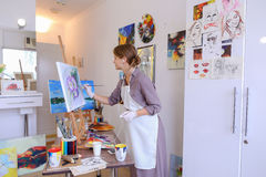 Beautiful young painter paints picture uses brushes and oil, and Stock Photography