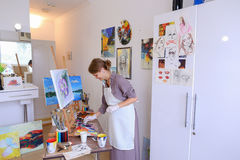 Beautiful young painter paints picture uses brushes and oil, and Stock Images