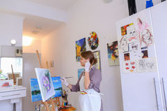 Beautiful young painter paints picture uses brushes and oil, and Royalty Free Stock Photography