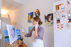 Beautiful young painter paints picture uses brushes and oil, and Royalty Free Stock Photos