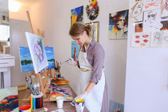 Beautiful young painter paints picture uses brushes and oil, and Stock Photos
