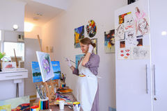 Beautiful young painter paints picture uses brushes and oil, and royalty free stock image