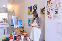 Beautiful young painter paints picture uses brushes and oil, and Stock Photo