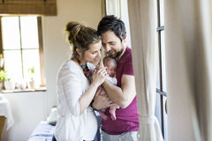 Beautiful young parents holding their cute baby daughter. Royalty Free Stock Photos
