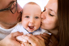 Beautiful young parents kissing their cute baby son Stock Photography
