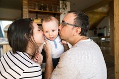 Beautiful young parents kissing their cute baby son. Beautiful young parents at home holding their cute baby son in the arms, kissing him on cheeks Royalty Free Stock Photos
