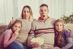 Beautiful young parents and their children are watching TV, eati. Young family watching television at home. Leisure and entertainment concept Stock Photo