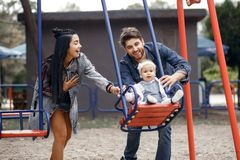 Beautiful young parents, walk with a child, swing him on a swing, have fun and enjoy each other, happy family for a walk. Beautiful young parents, walk with a stock images