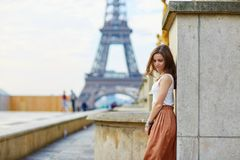 Beautiful young Parisian woman. In long skirt near the Eiffel tower on a summer day Stock Photo