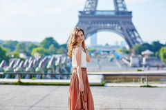 Beautiful young Parisian woman near the Eiffel tower Royalty Free Stock Image